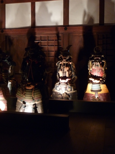 Quelques-unes des nombreuses armures (une quinzaine) de samurai alignées dans une salle. L'éclairage et leur disposition leur donnaient un air menaçant.