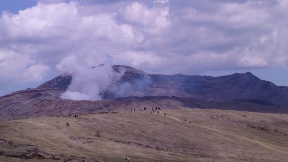 Le volcan est en arrière-plan, bien plus loin que les personnes sur la colline.